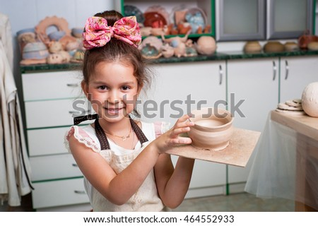 Little girl holding a cup of clay