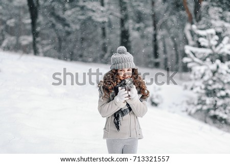 Little girl holding a cup of hot drink and smiling at the background of a winter forest. Christmas background.