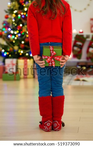 Little girl holding a gift behind his back near the Christmas tree