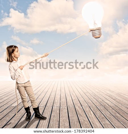 little girl holding a light bulb with a rope on a wharf - stock photo