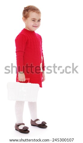 Little girl holding a medical bag with a red cross.Studio photo, isolated on white background.