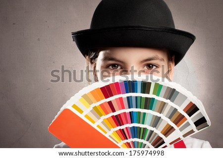 little girl holding a pantone palette on a gray background - stock photo