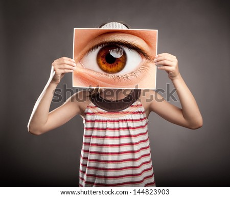 little girl holding a picture of an eye watching