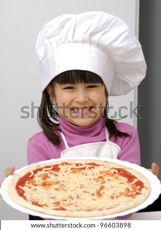 Little girl holding a pizza.Little girl with a chef cap holding a pizza. - stock photo
