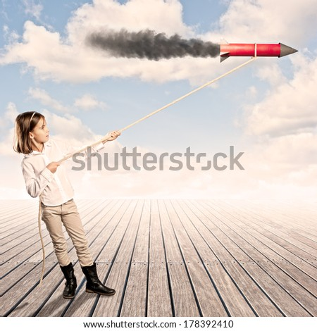 little girl holding a rocket with a rope on a wharf - stock photo