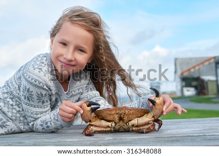 Little girl holding alive Norwegian Brown crab, Cancer pagurus,  edible crab, crab Tourteau leaning at table, outdoors - stock photo