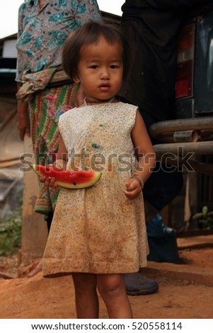 Little girl holding and eating watermelon in Hmong Village, Thailand. Chiang Mai.  31st October 2012.