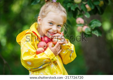 Little girl holding apples in the garden - stock photo