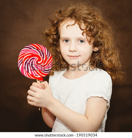 Little girl holding big colorful lollipop, toning in brown. - stock photo