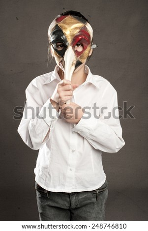 little girl holding carnival mask - stock photo