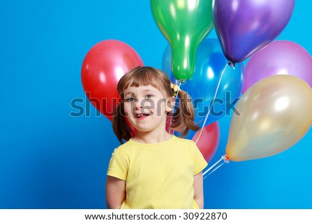 little girl holding colorful balloons on a blue background