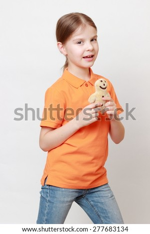 little girl holding cookie man toy - stock photo