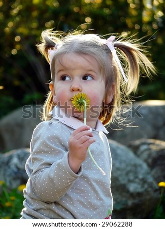 Little girl holding dandelion flower - stock photo