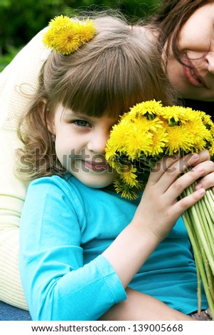 Little girl holding dandelions and sitting on her mom - stock photo