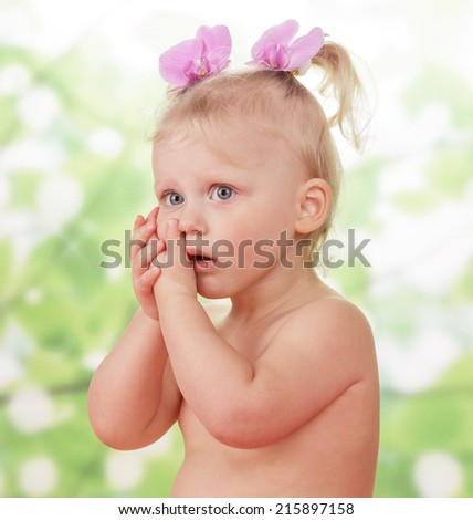 Little girl holding face with hand on green background - stock photo
