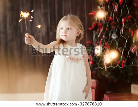 little girl holding firewors  on Christmas tree background - stock photo