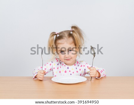 Little girl holding fork and spoon with , empty plate ready for food. - stock photo