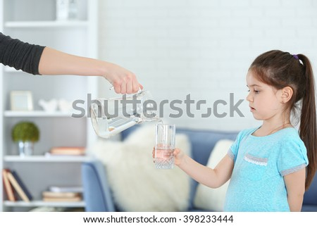 Little girl holding glass and adult woman pouring water from jug in living room - stock photo