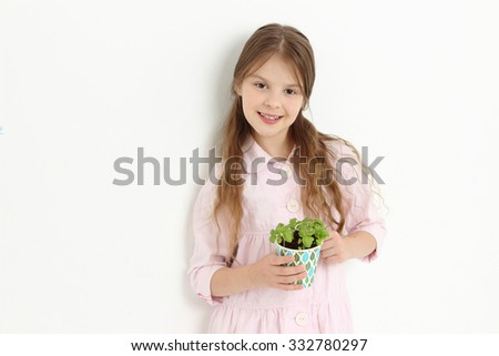 little girl holding green basil