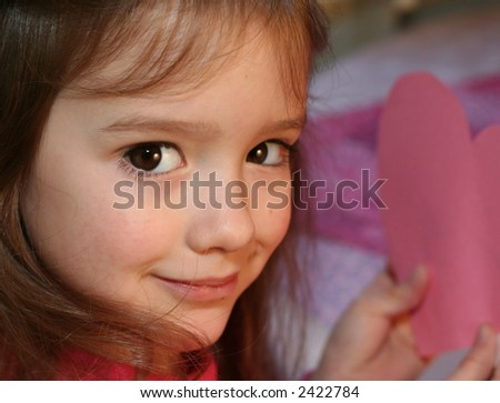 little girl holding hand-made valentine card