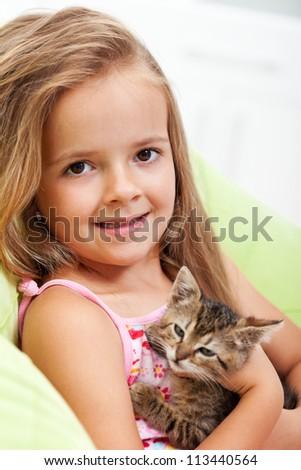 Little girl holding her kitten - shallow depth of field, closeup - stock photo