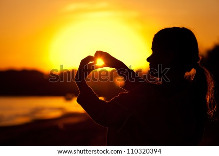 little girl holding in hands the setting sun - stock photo