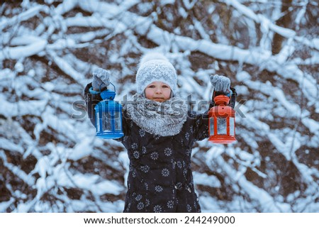 little girl holding in her hands two flashlight  in winter forest - stock photo