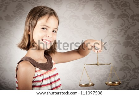 little girl holding justice scale - stock photo