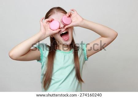 Little girl holding macaroons - stock photo
