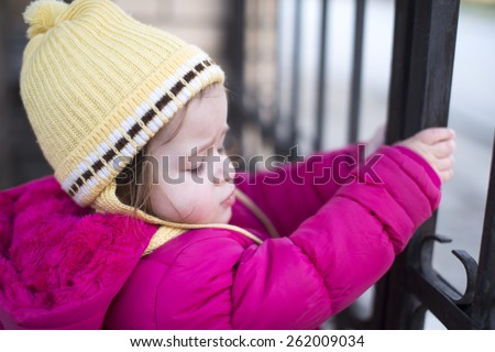 little girl holding on a metal gate in winter  - stock photo