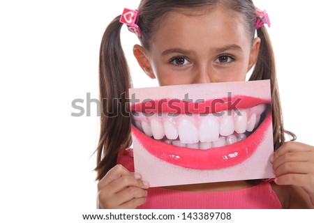 Little girl holding photo of mouth - stock photo