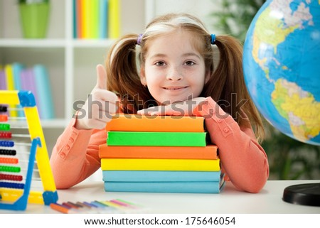 Little girl holding pile of books at home