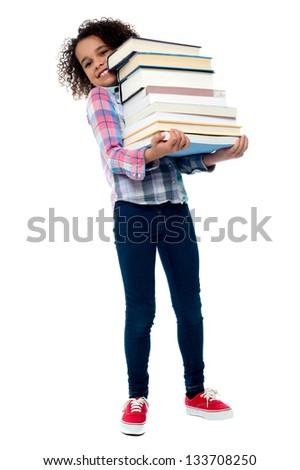Little girl holding pile of school books grinning happily. - stock photo