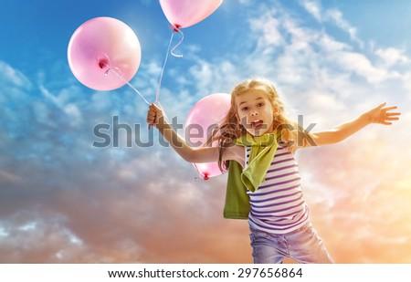 little girl holding pink balloons - stock photo