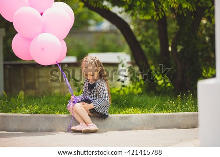 Little girl holding pink balloons