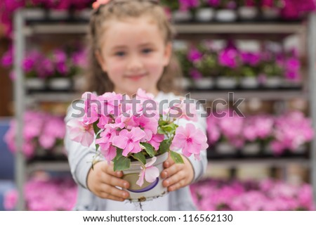 Little girl holding pink flowers out in garden center - stock photo