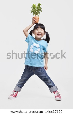 Little girl holding potted plant above her head, studio shot - stock photo