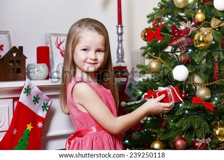 Little girl holding present box near fir tree on Christmas decoration background - stock photo