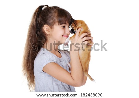 little girl holding puppy nose to nose - stock photo