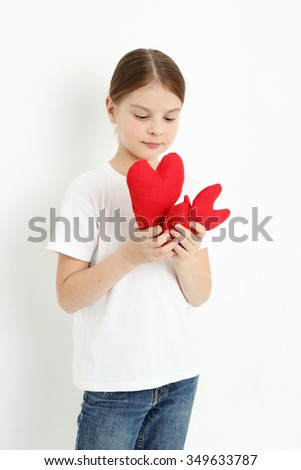 little girl holding red hearts