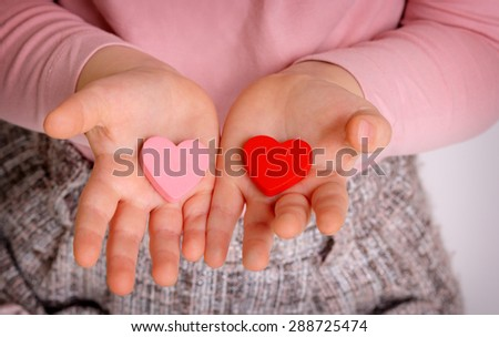 Little girl holding two wooden heart