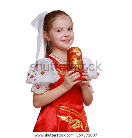 Little girl holding wooden doll in tradition style Hohloma (a brand of Russian traditional ornaments used for painting on wooden things)/Beautiful young girl with russian matreshka