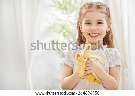 little girl holding yellow banana - stock photo