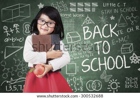 Little girl holds a book and apple back to school in classroom - stock photo
