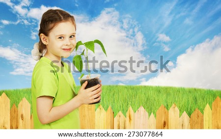 Little girl holds a pot with the seedling next to garden fence - stock photo