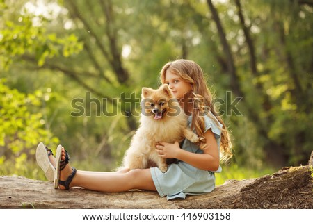 Little girl hug a pet. Girl sitting on a fallen tree and hugging the dog. Pedigree dogs Spitz.