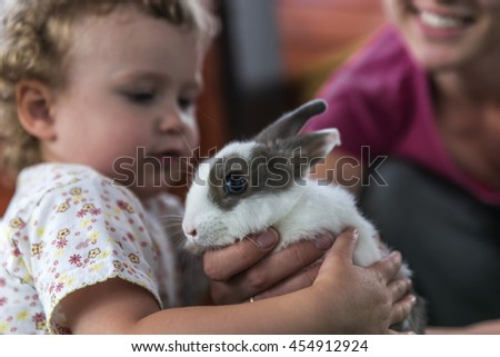 Little girl hugging a furry rabbit, under the supervision of mum