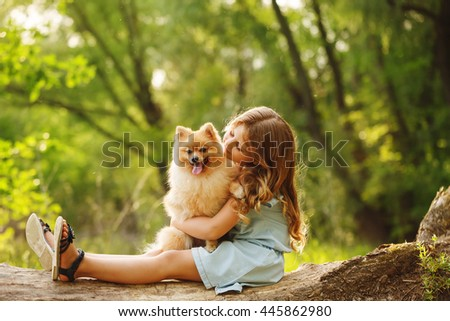 Little girl hugging a pet. Girl sitting on a fallen tree and hugging the dog. Pedigree dogs Spitz.