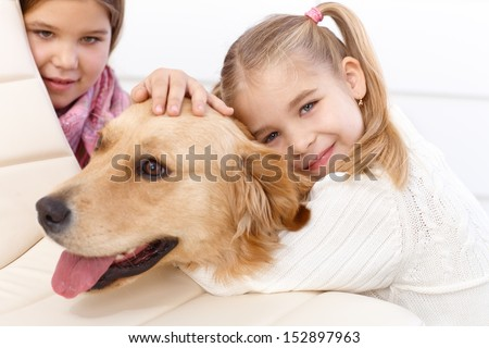 Little girl hugging golden retriever with love, older sister in background.