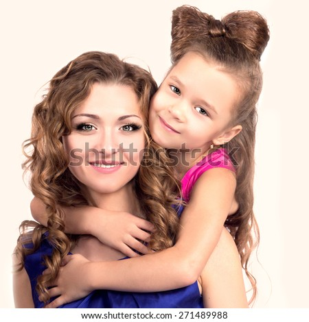 Little Girl Hugging her Beautiful Mother and Happy smiling together.  - stock photo